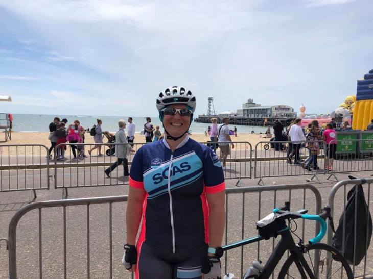 Tamsyn smiling whilst wearing SOAS cycling kit. She is standing by her bike next to Bournemouth beach.