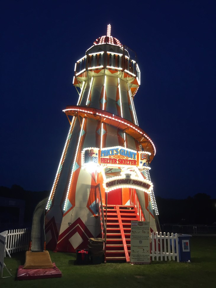 A traditional helter-skelter (slide going around a central tower) at night. It is decorated with lights.
