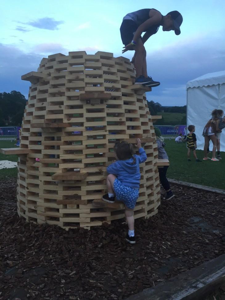Children climbing a beehive-shaped climbing frame made of wooden blocks.