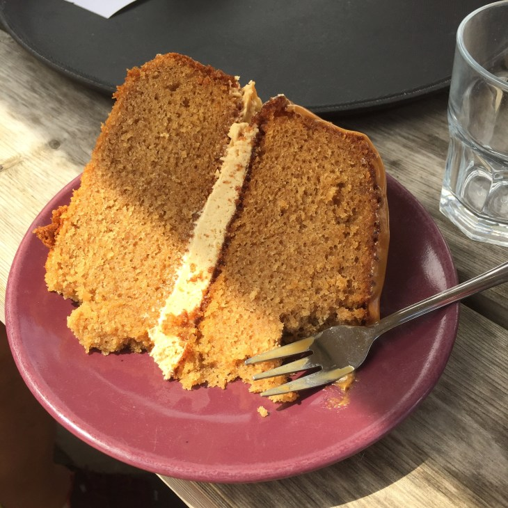 A large slice of caramel sponge cake with a cake fork.