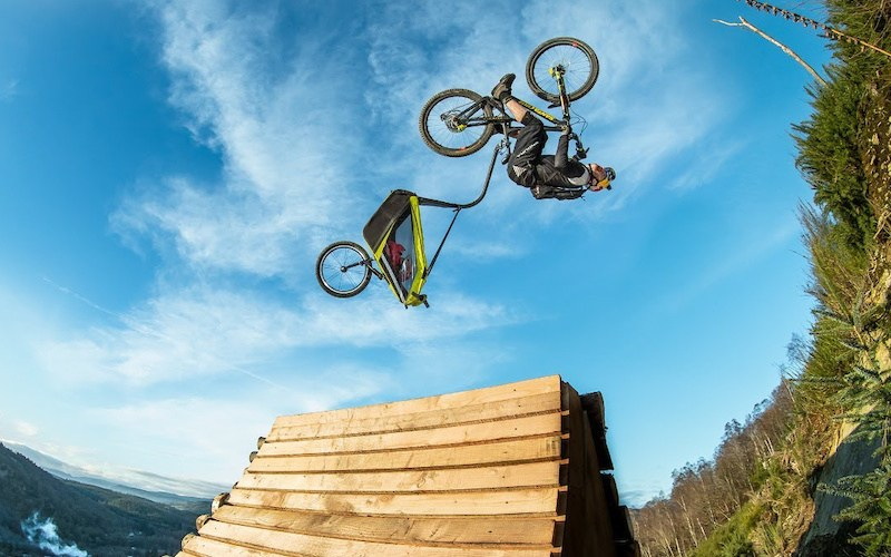 A man upside down in a jump on a bike pulling a trailer.