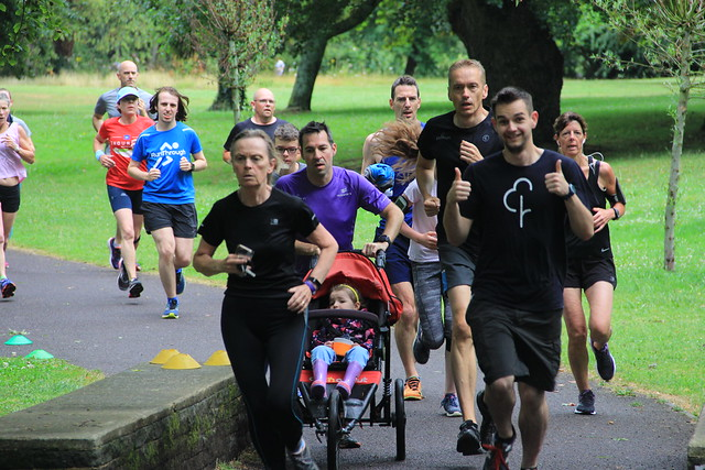 Stuart pushing M in her buggy in the first 5 minutes of Salisbury parkrun. They are surrounded by runners.