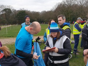 Tamsyn volunteering at parkrun. She can been seen talking to a pacer at parkrun.