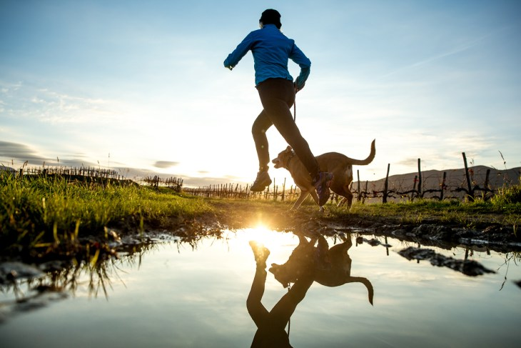 Woman running with her dog at sunrise.