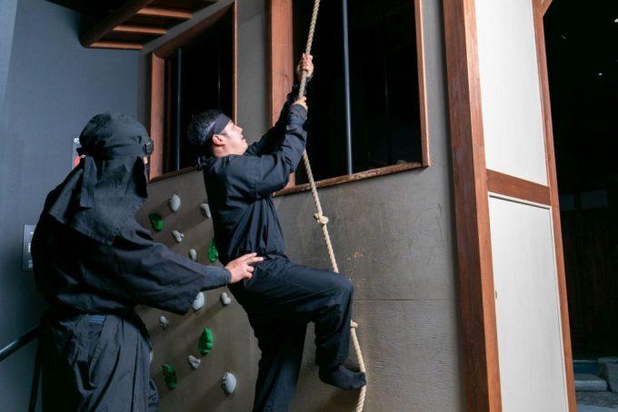 A ninja climbing a wall using a rope.