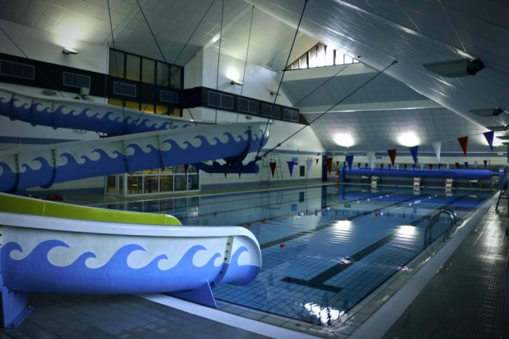 A flume (slide) curving over a swimming pool.