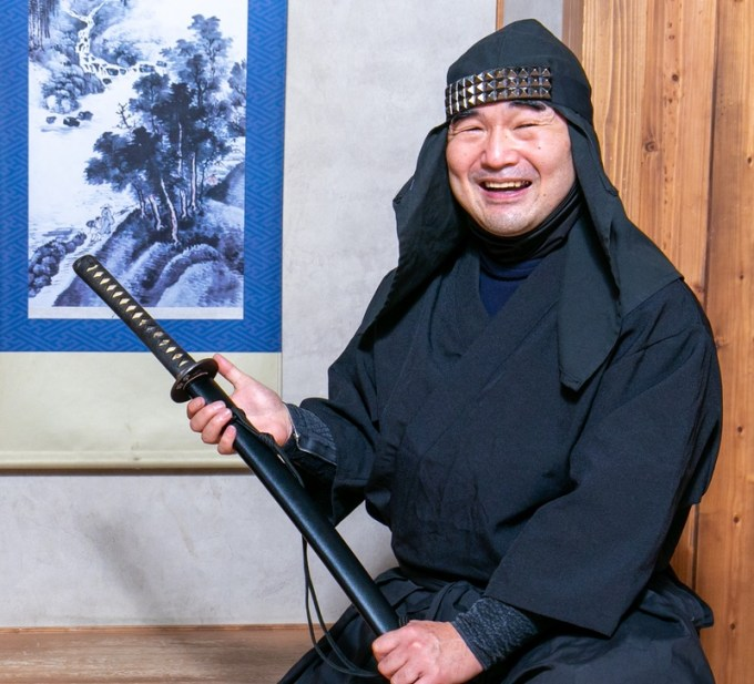 A smiling man wearing black ninja clothing and holding a katana (sword).