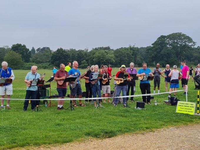 A group of around 10 people playing ukuleles on Southampton Common.