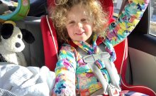 A kid in a red car seat