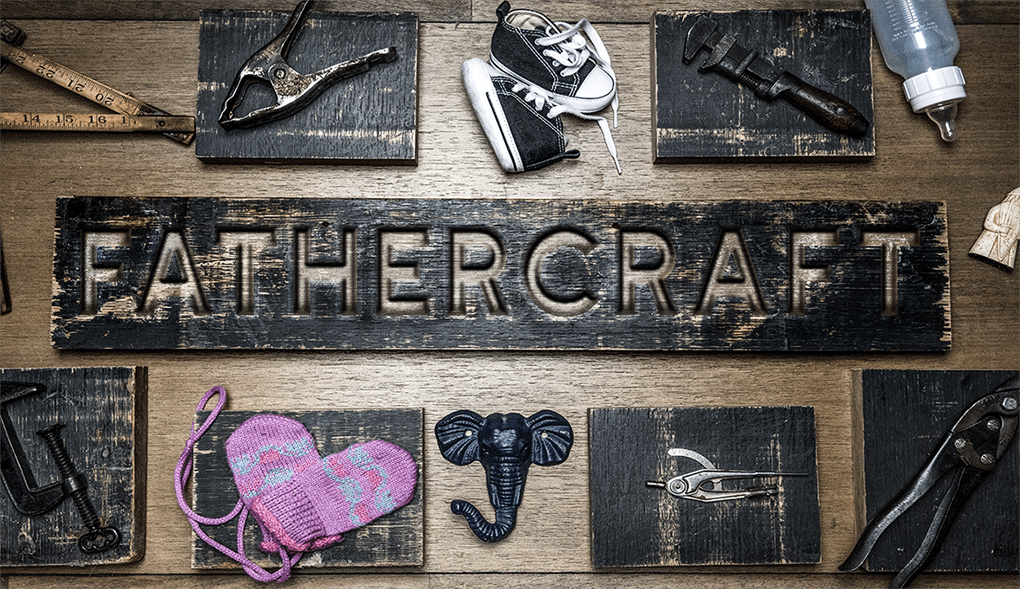 Fathercraft logo wood-burned on a table with tools and baby items