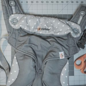 AN Ergobaby carrier on a measuring table with a clamp and scissors