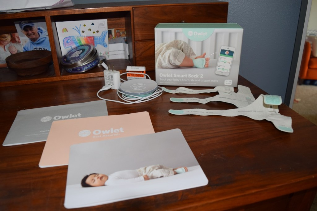Contents of the Owlet Smart Sock 2 box on a desk