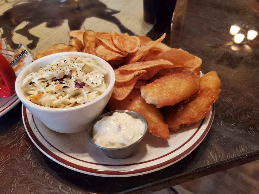 Cole slaw on the left, Fresh made kettle chips in the center and fried fish filets on the right side of the plate.  Served by the Stampede Saloon in Chugwater