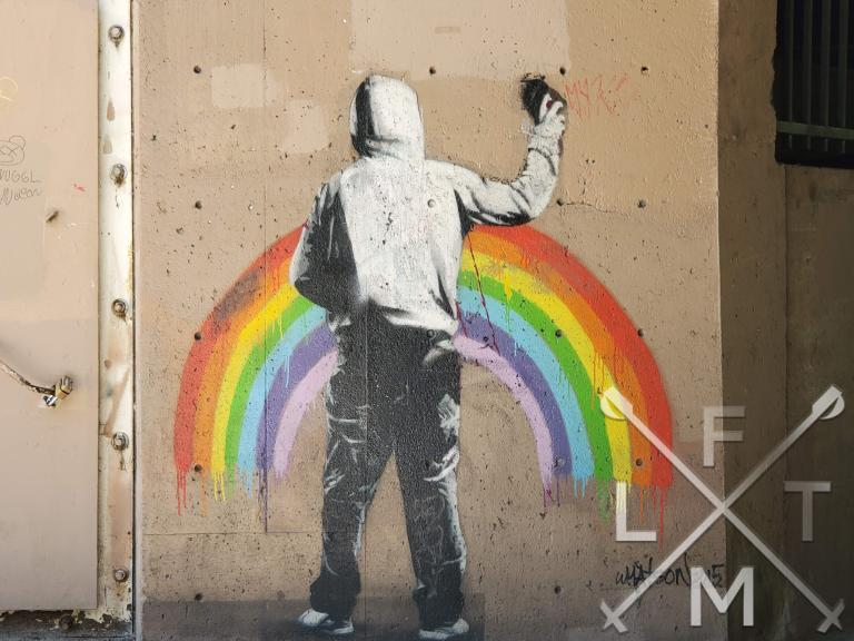 Street art image that has been spray painted on the concrete retaining wall.  The art depicts a hooded figure spray painting its own image of a rainbow