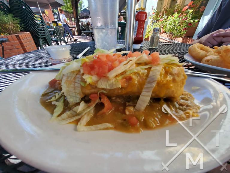 The beef chimichanga smothered in home made green chili with lettuce and tomato on the top.