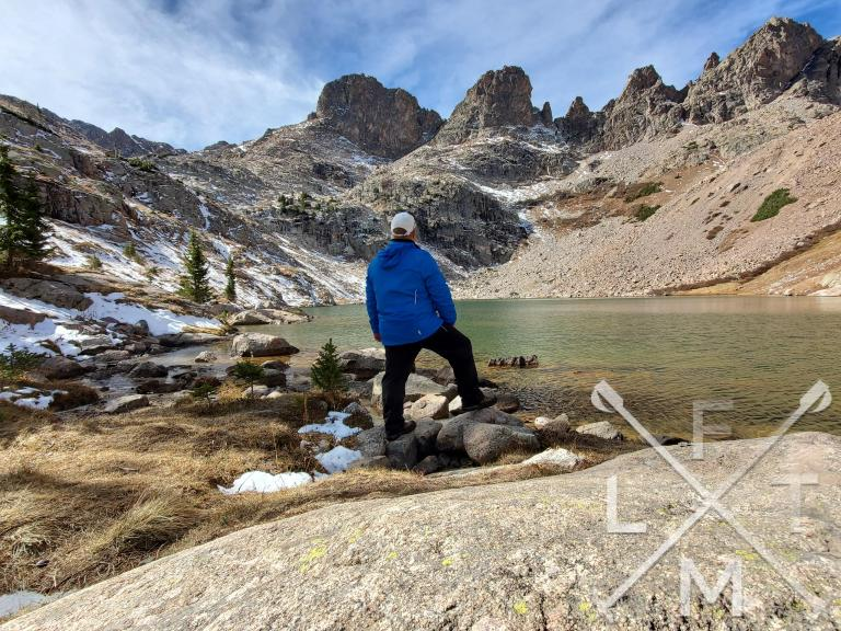 Me  standing next to an alpine lake in the Traverse pants.