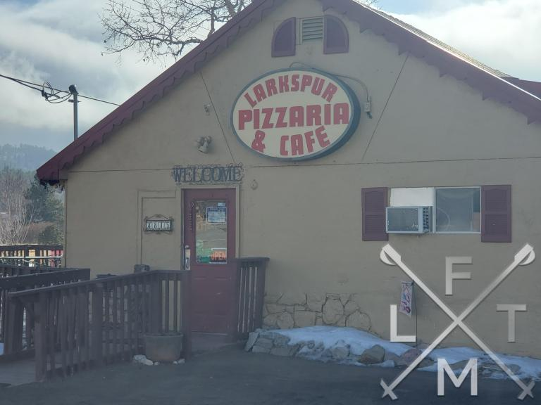 The sign for Larkspur Pizzaria and Cafe on the side of the modest building in Larkspur.