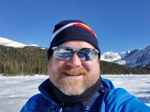 me smiling in front of a frozen lake with mountains and trees in the background.