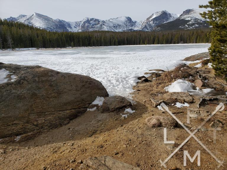 A dirt beach, frozen lake and mountains from Bierstadt Lake