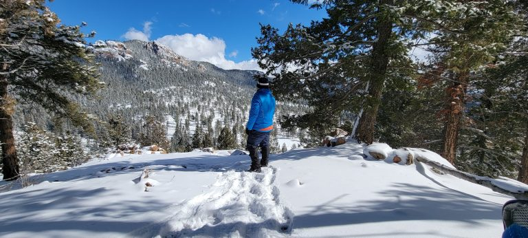 Me standing on a ledge in the snow overlooking a mountain with snow covered forest down below.  The picture is very peaceful and calm.  Calm is one of the stages I have found in the mental health benefits of hiking.