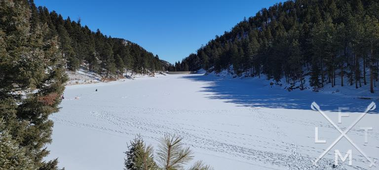 Palmer Lake #2 covered with snow and surrounded by tree lined hills on the Chautauqua Mountain trail.