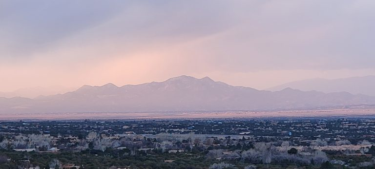 A distant mountain is engulfed in a pinkish colored cloud.  The mountain outline is visible but through a pink haze on the Sun Mountain Trail.