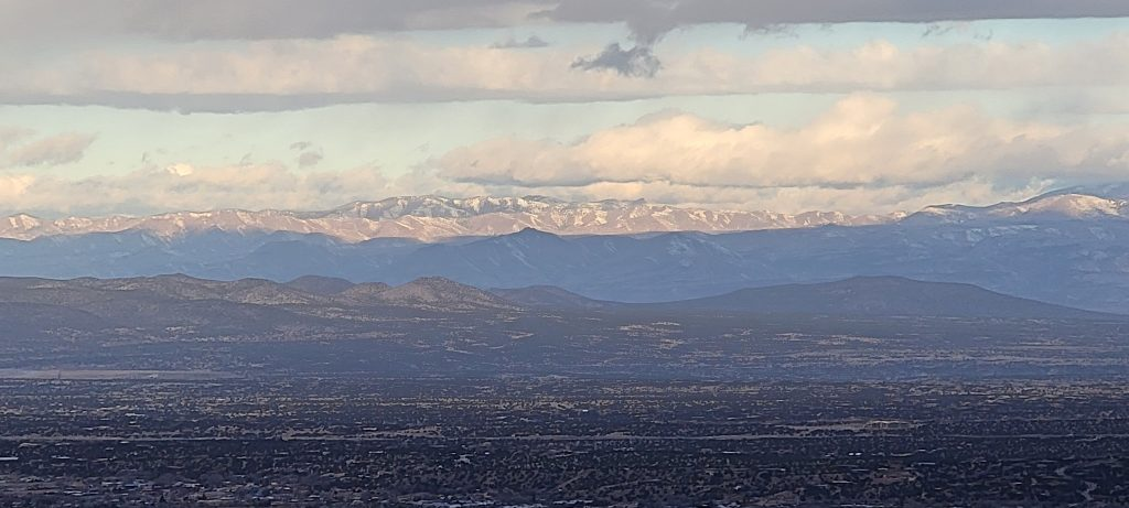 A snow capped mountain range on the outskirts of Santa Fe from about halfway up the Santa Fe Trail.