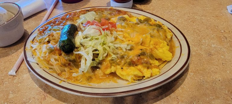 The huevos rancheros from Weck's in Santa Fe.  Scrambled eggs covered in green chili and cheese.  Beans and hash browns round out the plate that is topped with cheese and lettuce and tomato.