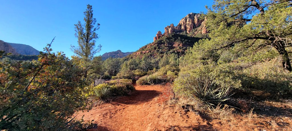 An example of the dirt trail on the Broken Arrow trail.   Trees and bushes surround the trail with large rock formations in the background.