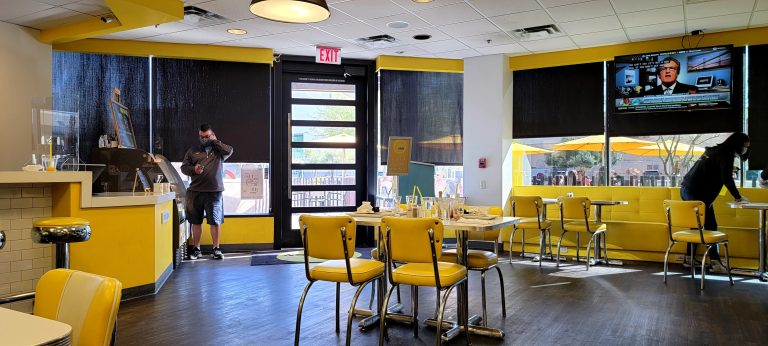 The inside of Over Easy in Phoenix has a bright yellow and modern design.  Yellow medal and vinyl chairs as well as yellow counters and bar stools make it feel like a bright sunny day.