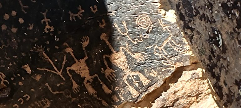 Some of the intricate carvings on the rock at Newspaper rock in the Petrified Forest National Park.  This carving has several people and animals.