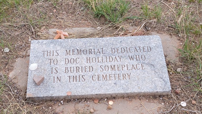 A memorial plaque announcing that while at Doc Holiday's Grave this might not actually be Doc Holiday's Grave and he may be burried somewhere in the cemetery but not necessarily at this spot.