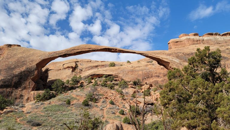 Landscape arch stretching 306 feet across the blue sky from the Devils Garden Trail at Arches National Park.