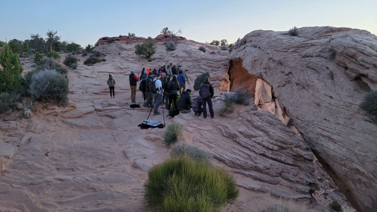 The large group of photographers waiting for the Sunrise at Mesa Arch.  They are huddled together next to each other by the arch.