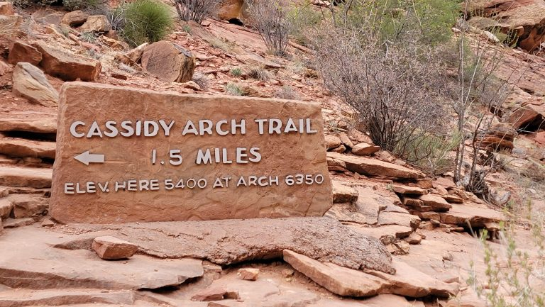 The sign for Cassidy Arch sits on a rock tablet in the middle of the Grand Wash Trail.