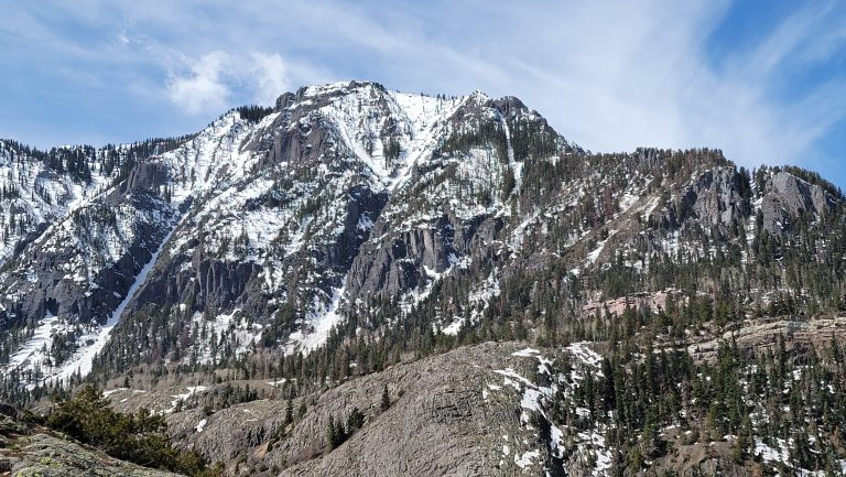 Large snow capped mountain sits above rolling hills on the Ouray Perimeter trail.