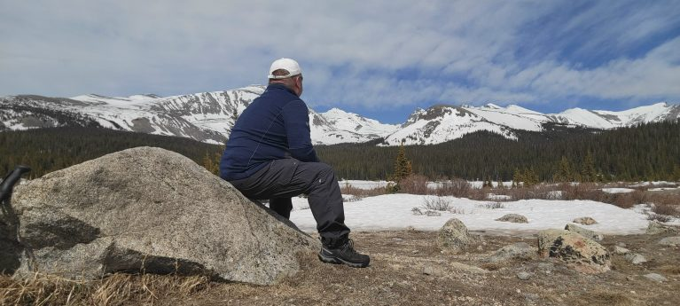 Me sitting on a rock looking out over snow capped mountain peaks as part of my Kuhl Renegade Cargo Convertible Pant Review.