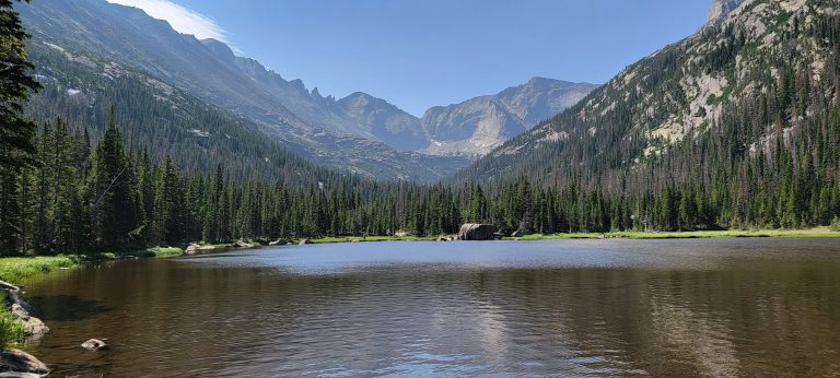 Jewel Lake is a smaller pond with flat water and surrounded by pine trees with large rocky mountains in the background. This is the sixth and final stop on my Bear Lake Trailhead: Lakes Loop tour.