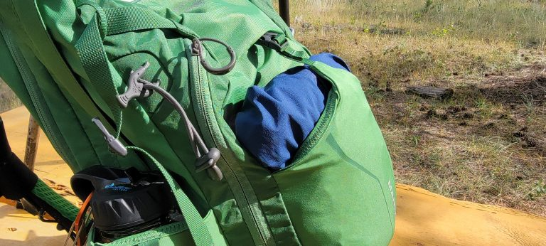 a rain jacket folded and stuffed in the open back pouch on the Osprey Manta 24 backpack.