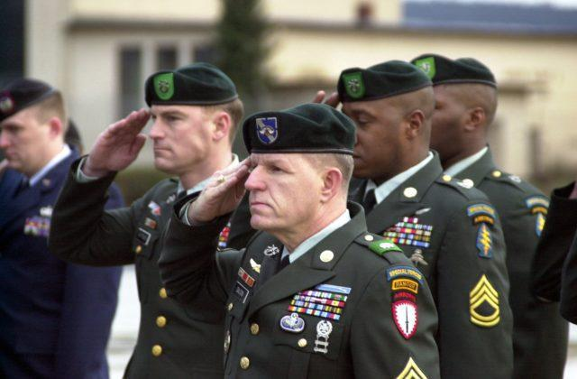 During a Fallen Soldier Ceremony at Ramstein Air Base, Germany, one of the flag draped coffins (not shown) containing the remains of one of 6 coalition soldiers, killed in Kuwait during a training exercise March 12 2001, is rendered a salute from a formation of Army Green Berets, as it is carried off a C-17 Globemaster III aircraft (not shown) for transportation to the Landstuhl Regional Medical center for identification. (Duplicate image, see also DFSD0201414 or search 010315F2454T504)