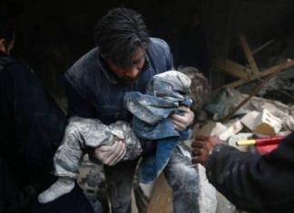Homem sírio retira criança de destroços de prédio após ataques na cidade de Duma