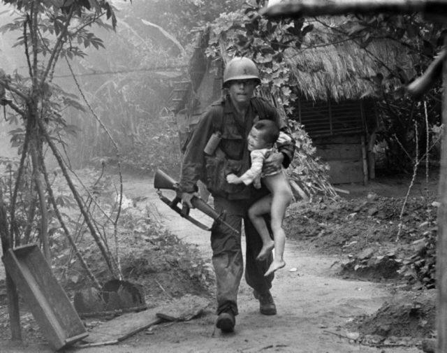 Um fuzileiro americano carregando uma criança