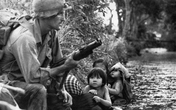 Um soldado dos EUA protege uma familia vietnamita do Sul.