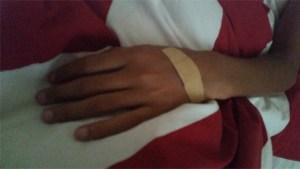 Beige plåster på brun hand