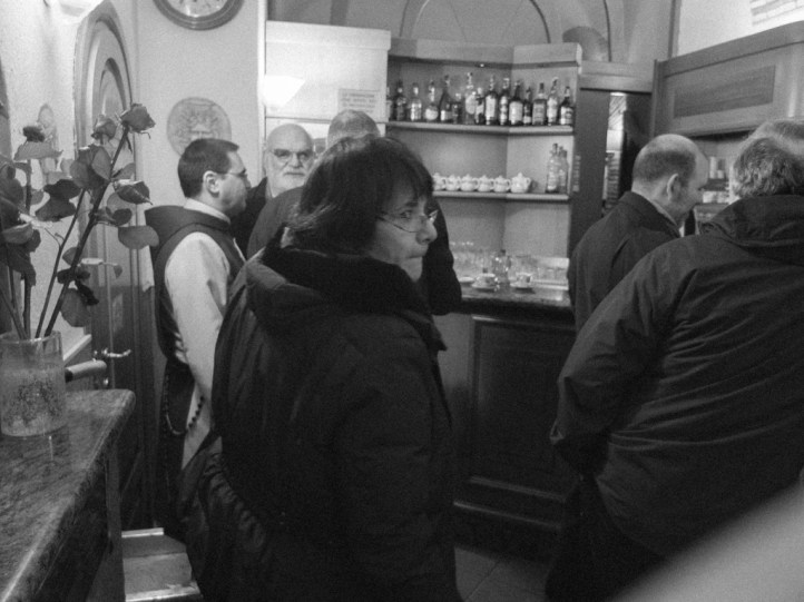 "Priest mingling and having coffee at a bar near Arco del Lauro before ""going to work""."
