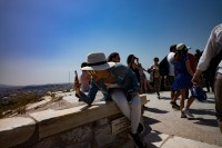 Tourist taking a picture of her partner on top of Acropolis