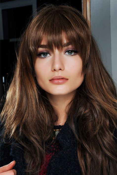 5 Mid-back length brunette hairstyle featuring modern bangs with a curve