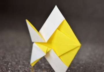 yellow and white origami fish on gray background