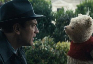 Man in hat with confused look at stuffed toy yellow bear with red shirt