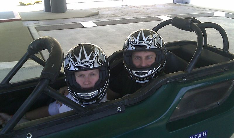 two black-helmeted bobsled participants in a green bosled